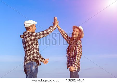 Two People Expressing Happiness and Enjoying Success Touching Hands Arms Raised Casual Jeans Style Clothing Blue Sky and Shining Sun Background