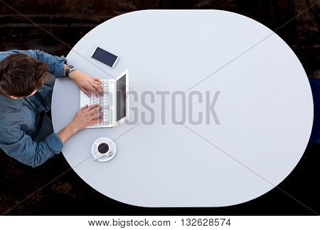 Grey Office Round Table and Man Working on Computer Top View Casual Clothing Typing on Keyboard with Marketing Chart on Screen