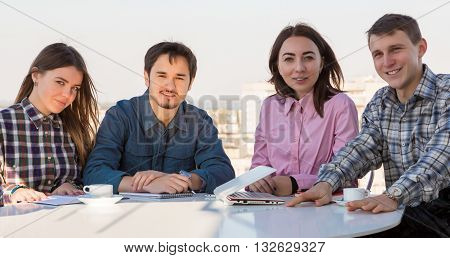 Group of Young Casual Dressed People on Informal Business Meeting at White Rounded Table Roof Top Cafe Terrace Urban Landscape Background