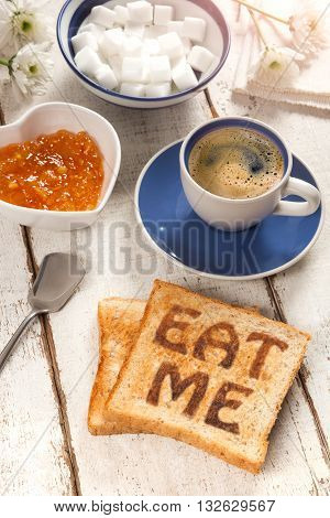 Breakfast, coffee, jam and toast with the text eat me