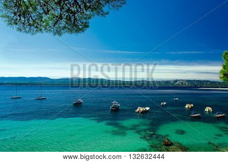 beautiful scene of yachts and boats in crystal water bay on island Brac Croatia with Zlatni Rat beach