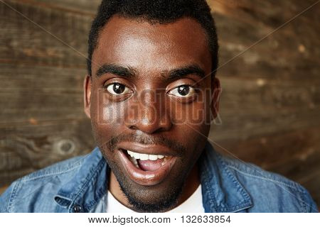 Close Up Portrait Of Successful Young Black Entrepreneur Wearing Denim Shirt Looking And Smiling At