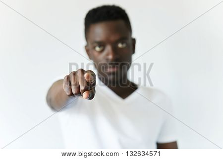 Close Up Shot Of African Man Pointing A Finger Right At The Camera. Young Black Male Wearing White T
