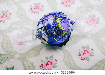 KILCHBERG SWITZERLAND - MARCH 20 2014: Lindt Lindor chocolate truffle on a luxury silk background. Lindt is one one of the lastgest luxury chocolate and confectionery company worldwide