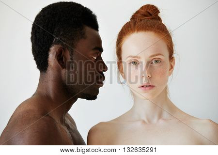 Coffee And Milk. Portrait Of Young Mixed Race Couple Posing Naked Against White Studio Wall. Profile