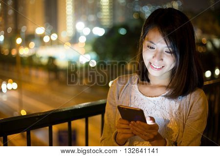 Woman sending sms on mobile phone at outdoor