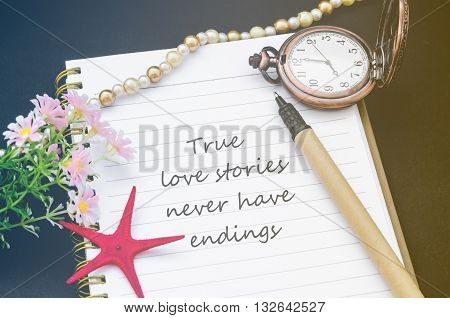 True love stories never have endings handwriting on diary note with vintage pocket watch in filter.