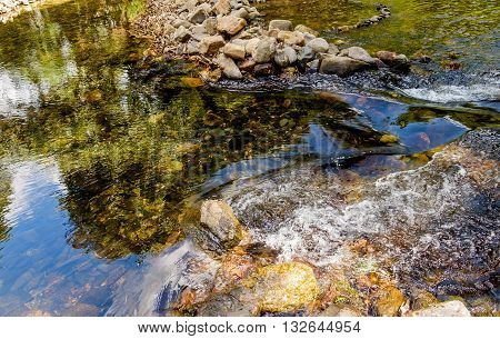 Yellow rocks are seen through the clear water flowing Khao Sok National Park Surat Thani Province Thailand.