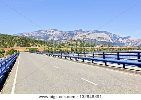 Modern Road Bridge Bordered by Blue Railings Crosses the Wide River Towards Farms and the Mountains Beyond
