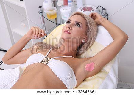 Beautician makes waxing armpit hair, beautiful blonde woman in a beauty salon.