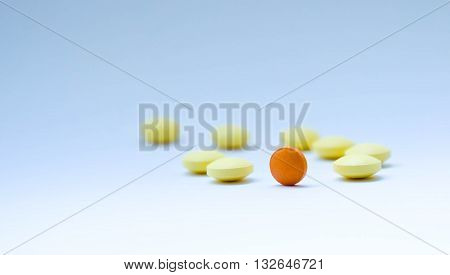 tablets, yellow and one orange, orange symbolizes the sun, everything turns around pharmacology, blue background similar to the sky