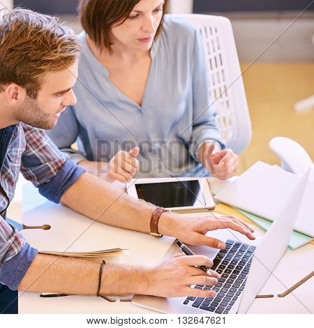 Square image of a male student and businessman typing on his notebook as his female partner explains details of the situation to him from her tablet.