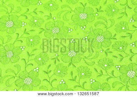 Repeating Design of Stylised Embroidered Flowers and Leaves on a Synthetic Background.