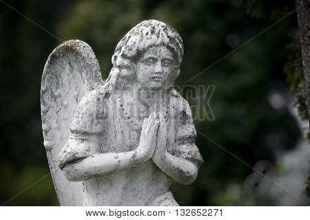 Old cemetery angel sculpture made of stone in London graveyard