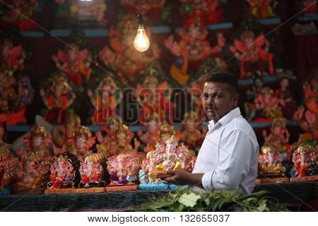 Pune India - September 16 2015: A man selling Lord Ganesh idols on the eve of Ganesh festival in India. The festival involves thousands of visitors from all over the world every year in the main celebration city - Pune.