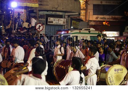 Pune India - September 27 2015: People in India dancing on the streets on the beats of traditional percussion instrument dhol during a huge procession in the Ganesh festival
