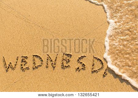 Wednesday -  word drawn on the sand beach with the soft wave.