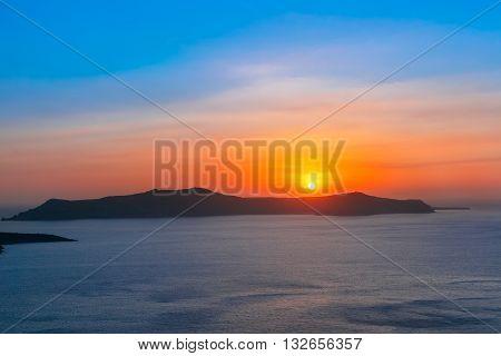 Beautiful vibrant sunset over the sea and island Thirasia, Santorini, Greece