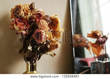 bouquet of dried roses in golden vase
