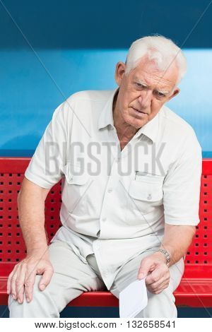 Retired Man Sitting On Bench