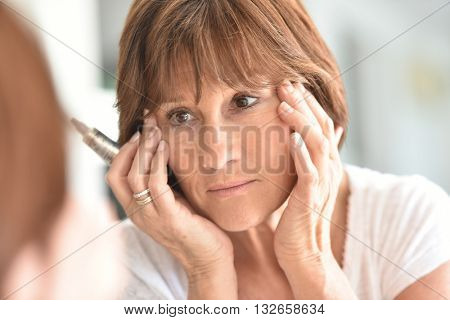 Senior woman applying eye concealer