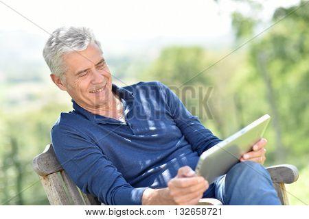 Senior man websurfing on tablet outside