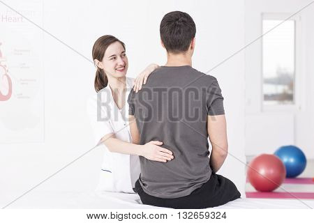 Young smiling masseur giving a back massage to her patient sitting on a massage table
