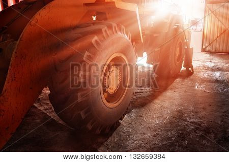 The big yellow wheel of heavy tractor in the sun.