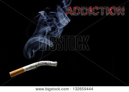 Burned cigarette, smoke and text addiction on black background