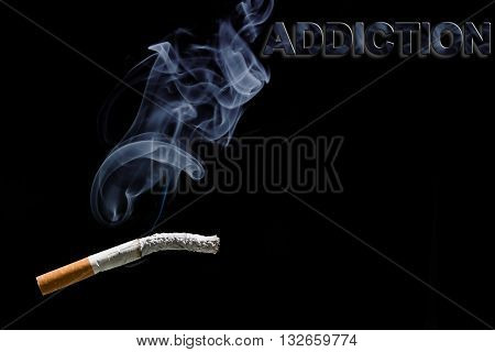 Burned cigarette and text addiction on black background