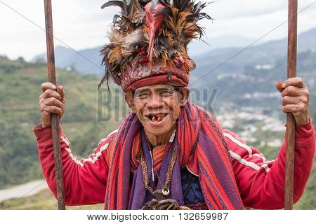 BANAUE PHILIPPINES - JANUARY 24 2014 : Portrait old Filipino man of Ifugao mountain tribes in national dress next to rice terraces. Ifugao - the mountain people in the Philippines.