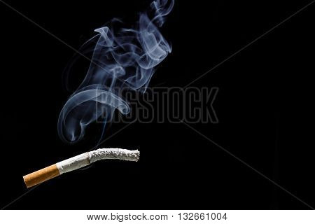 Cigarette burning and smoke with black background