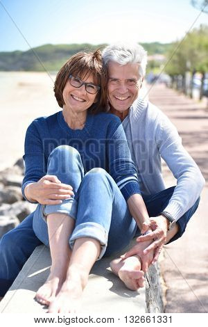 Happy senior couple sitting by the beach