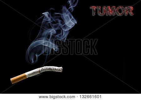 Burned cigarette and text tumor on black background