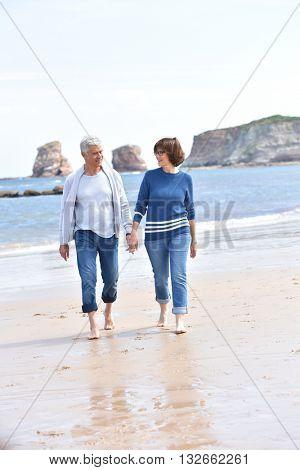 Senior people walking on sandy beach