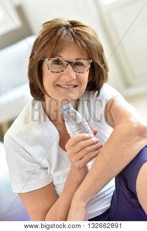 Senior woman in fitness outfit holding bottle of water