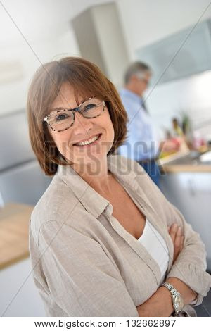 Portrait of smiling senior woman, husband in background