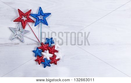 Stars in exploding pattern with USA national colors on rustic white wooden boards. Fourth of July holiday concept for United States of America.