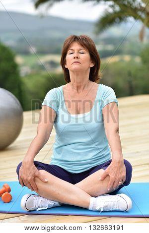Senior woman doing relaxation exercises outside