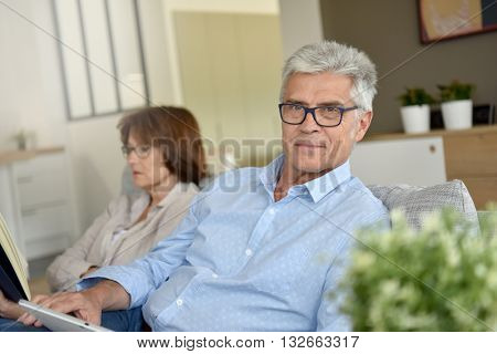 Senior people relaxing in couch at home
