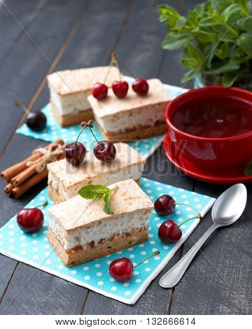 Meringue cakes and cherries with cup of tea