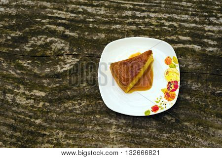 Flan - delicious creme dessert with caramel sauce.French creme caramel dessert or flan with strawberry and mint on the wooden background