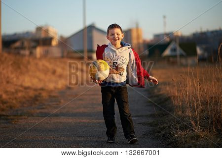 boy in a red jacket, pants, sneakers plays soccer, enjoys running, kicking the ball, smiling