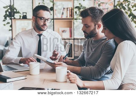 I need your signature. Confident young man signing some document while sitting together with his wife and man in shirt and tie