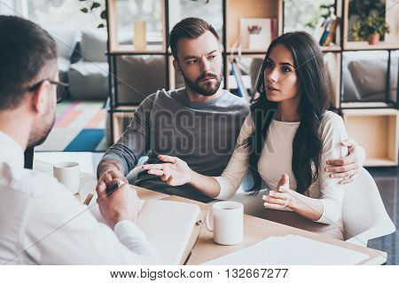 Sharing problems with doctor. Young couple telling their problems to psychologist while sitting together at the desk