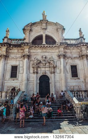 Dubrovnik Croatia - August 26 2015. Tourists sits on the stairs of Baroque church of Saint Blaise's located on the Old Town of Dubrovnik
