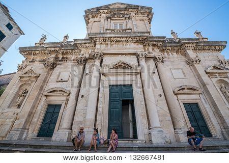 Dubrovnik Croatia - August 26 2015. Tourists sits on the stairs of Assumption of the Virgin Mary cathedral located on the Old Town of Dubrovnik