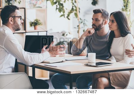 They need an expert advice. Young couple sitting together at the desk and listening to their financial advisor