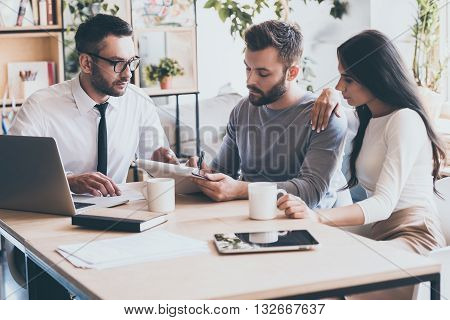 And your signature here. Confident young man signing some document while sitting together with his wife and man in shirt and tie