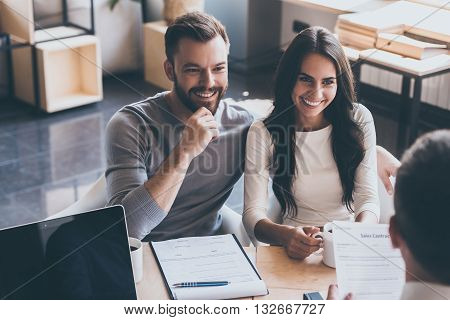 Good deal. Young loving couple bonding to each other and looking at man sitting in front of them at the desk